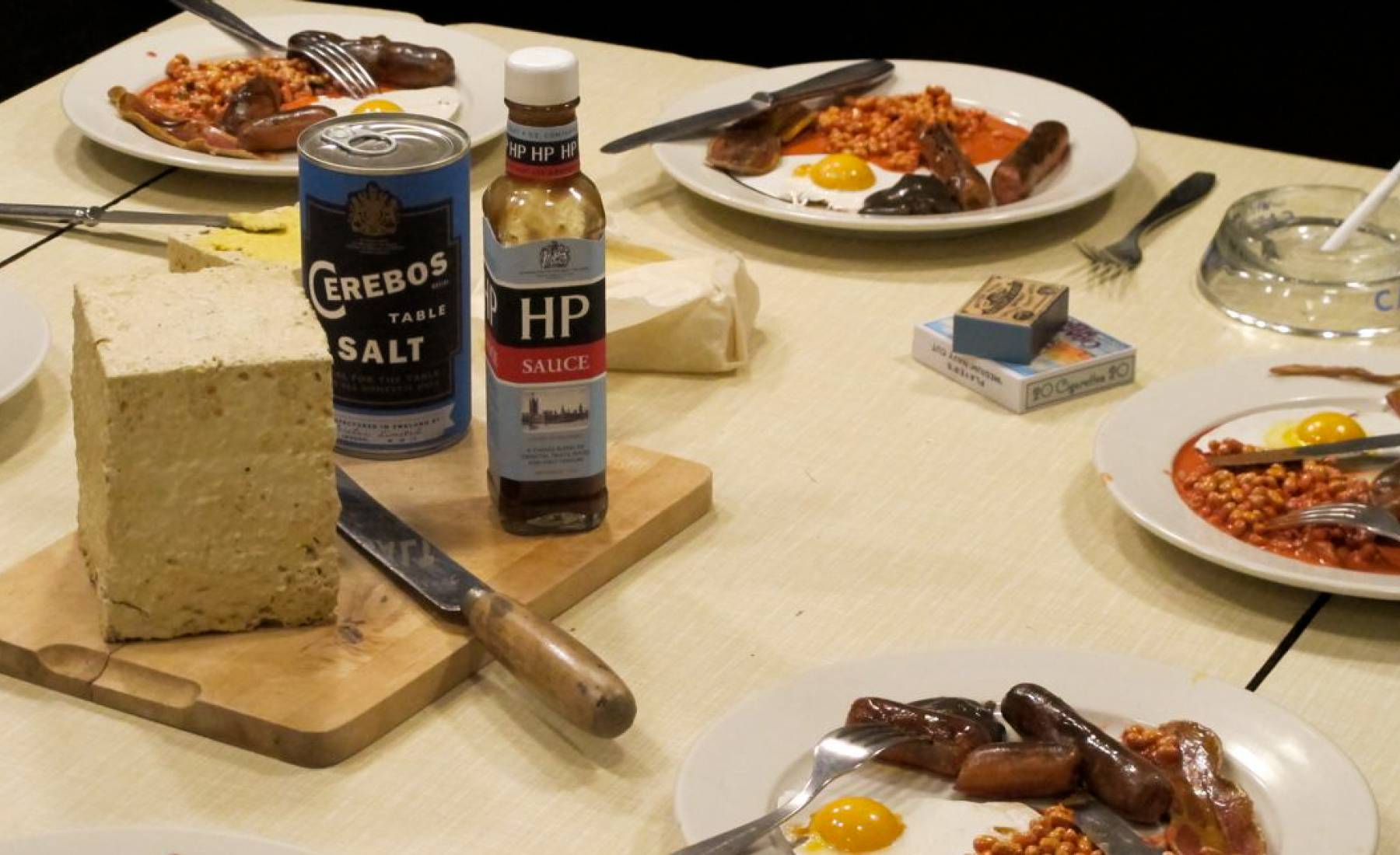 submarine realistic fake food, fried breakfasts on a table.1960's. bread, sausages, eggs, hp sauce, baked beans